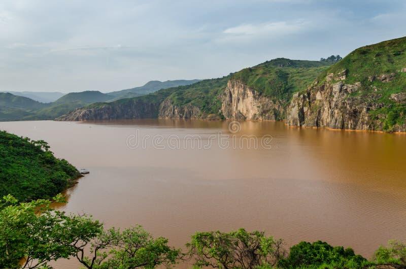 Ajardine incluyendo el agua marrón tranquila del lago Nyos, famosa por la erupción con muchas muertes, Ring Road, el Camerún del  imagen de archivo