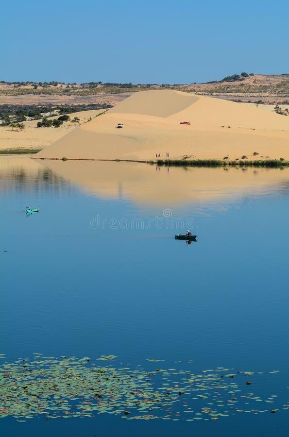 Ajardine la duna de arena blanca con el pescador y el bote pequeño en azul imagen de archivo