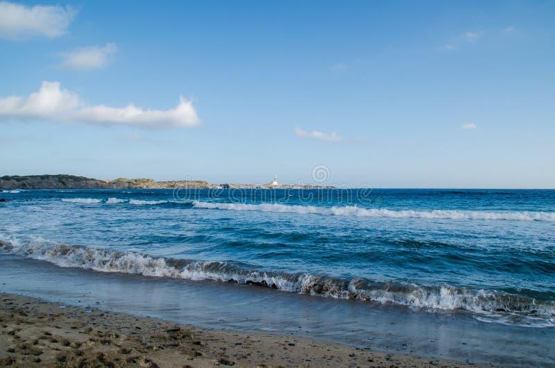 Ajardine la fotografía de uno de los lugares más conocidos de Menorca en la costa con un faro foto de archivo