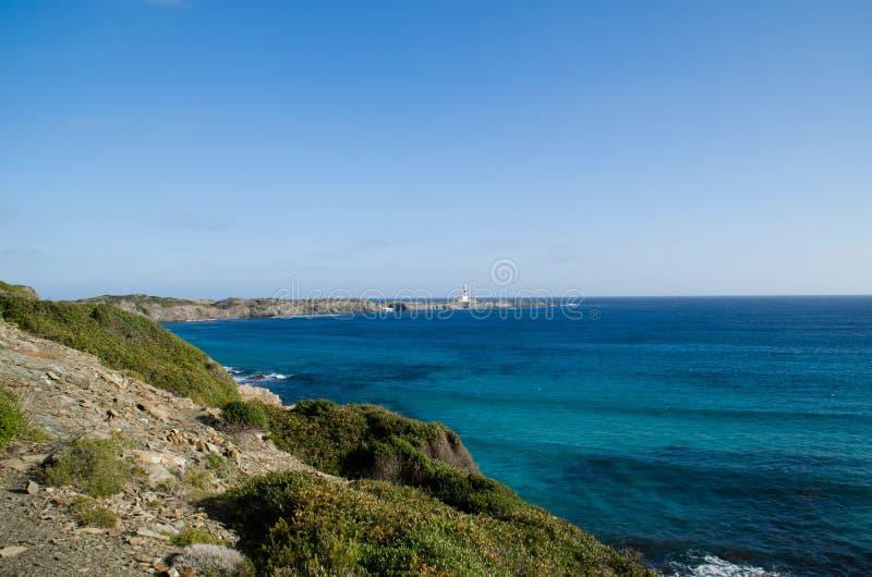 Ajardine la fotografía de uno de los lugares más conocidos de Menorca en la costa con un faro fotografía de archivo