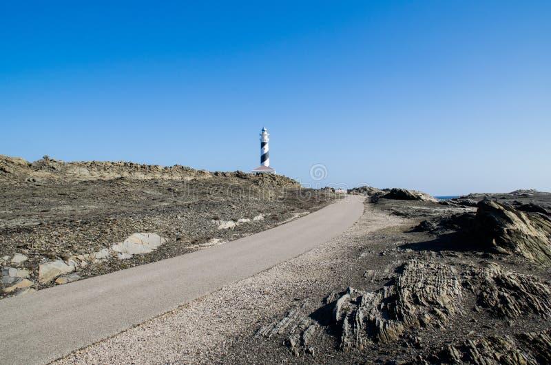 Ajardine la fotografía de uno de los lugares más conocidos de Menorca en la costa con un faro fotos de archivo libres de regalías