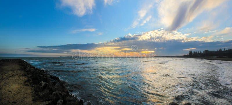 Ajardine la puesta del sol en el mar y el embarcadero Panorama imagen de archivo