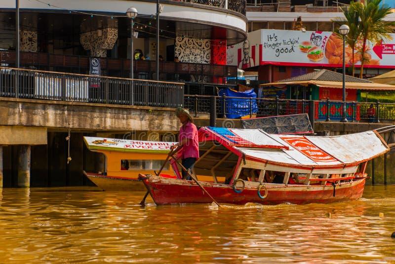 Ajardine la vista de la ciudad y del río de Sarawak Barco tradicional local para los turistas Kuching, Borneo, Malasia imagen de archivo libre de regalías