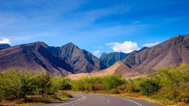 Ajardine la vista de montañas en Maui del oeste y el camino imagen de archivo