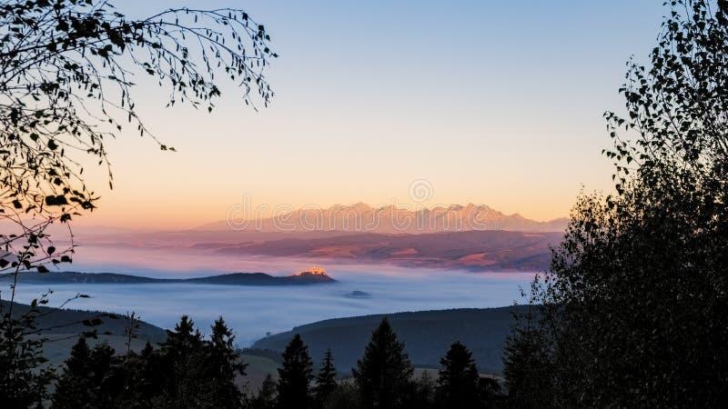 Ajardine la vista del castillo de Spis y de las altas montañas de Tatras en el sunri imagenes de archivo