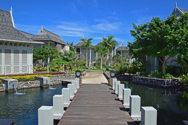 Ajardine la vista del hotel turístico exclusivo hermoso con el pequeño puente de madera que conecta la calzada con los chalets imagenes de archivo