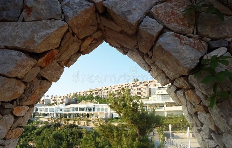 Ajardine a negligência do território do hotel através do arco foto de stock