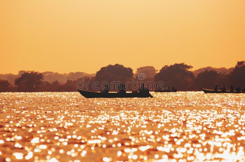 Ajardine no por do sol dos barcos com os pescadores que pescam em Pantanal foto de stock