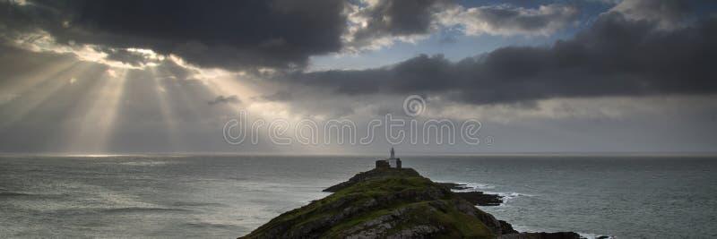 Ajardine o panorama do farol dos Mumbles em Gales com raios de sol imagens de stock royalty free