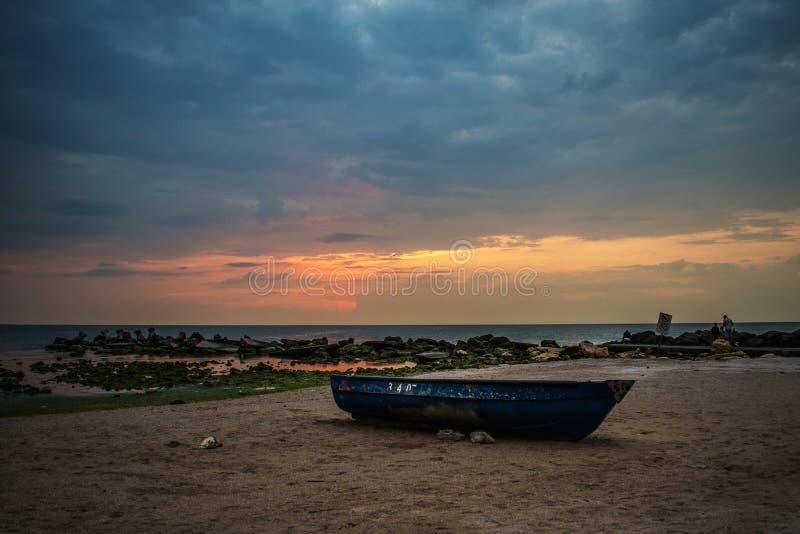 Ajardine um nascer do sol bonito no oceano Um c?u dram?tico Barco e rochas perto da costa fotografia de stock