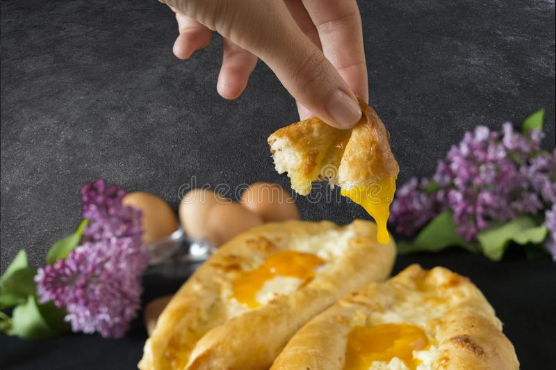 Adjara khachapuri with two types of cheese. Ajarian khachapuri with two types of cheese. Delicious pastries. The photo with the hands stock photos