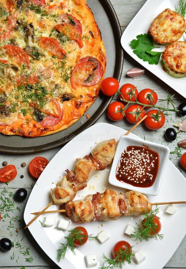 Ajo de las aceitunas de los tomates del Bbq del kebab de la pizza en la tabla rústica de madera imagen de archivo