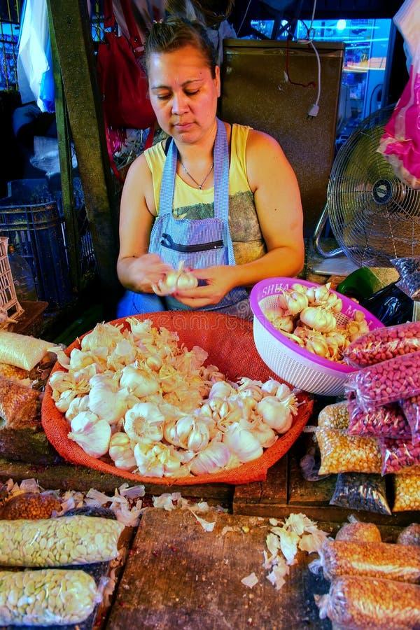 Ajo local de la peladura de la mujer en Mercado Cuatro en Asuncion, Paragu imagenes de archivo