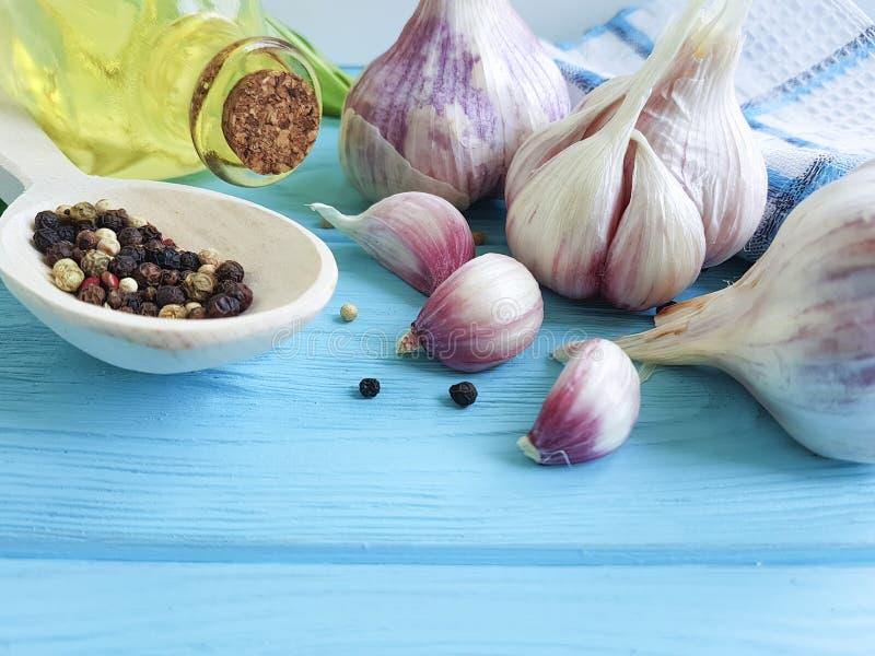 Ajo, pimienta negra, madera rustictable de aderezo del azul del aromaticon de la nutrición del aceite foto de archivo