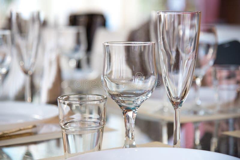Ajournez l'arrangement dans le restaurant, y compris des verres pour le vin, champagne et cognac, serviettes et plats pour des in photos libres de droits
