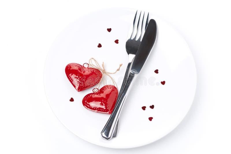 Ajournez l'arrangement pour la Saint-Valentin avec la fourchette, le couteau et les coeurs photo stock