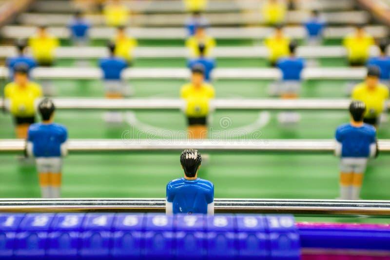Ajournez la partie de football, table du football avec les joueurs jaunes et bleus Jeu de table du football avec les joueurs jaun photo stock