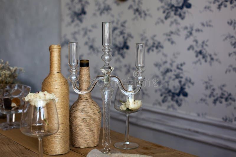 Ajournez la portion avec le chandelier, les bouteilles et le verre à vin en verre avec image stock