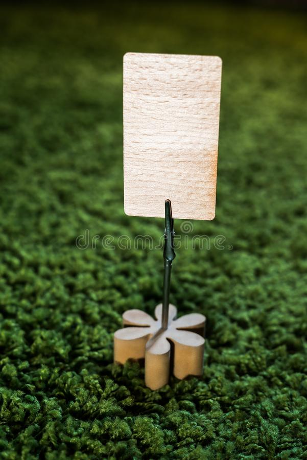 Ajournez le support de note de carte d'agrafe avec la fleur en bois et une carte vierge pour la rédaction publicitaire sur le fon photos stock