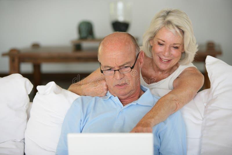 Ajouter aînés à la maison à l'ordinateur portable images libres de droits