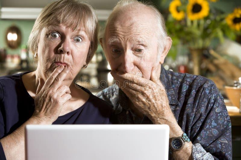 Ajouter aînés perplexes à un ordinateur portable photo stock