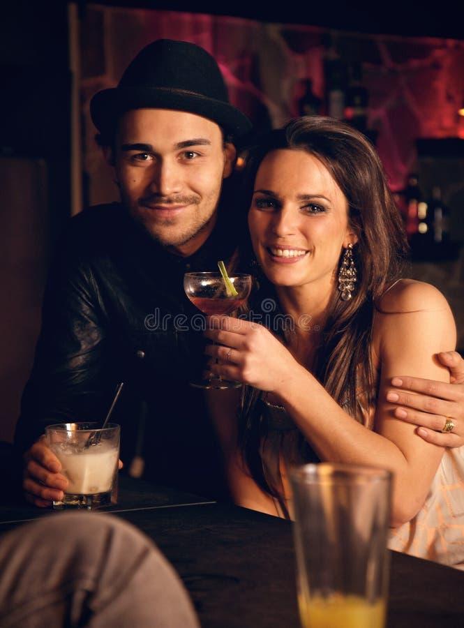 Couples attrayants appréciant leurs boissons et souriant à vous photos stock