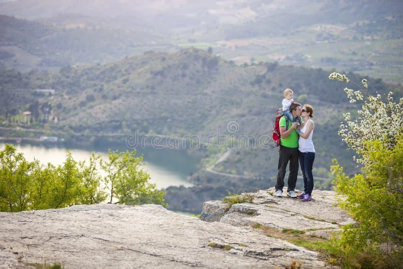 Ajouter au bébé garçon se tenant sur la falaise et des baisers image stock
