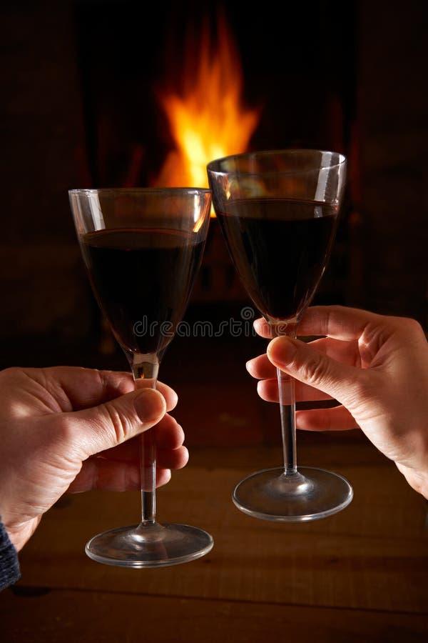 Ajouter au verre de vin détendant par le feu photo libre de droits