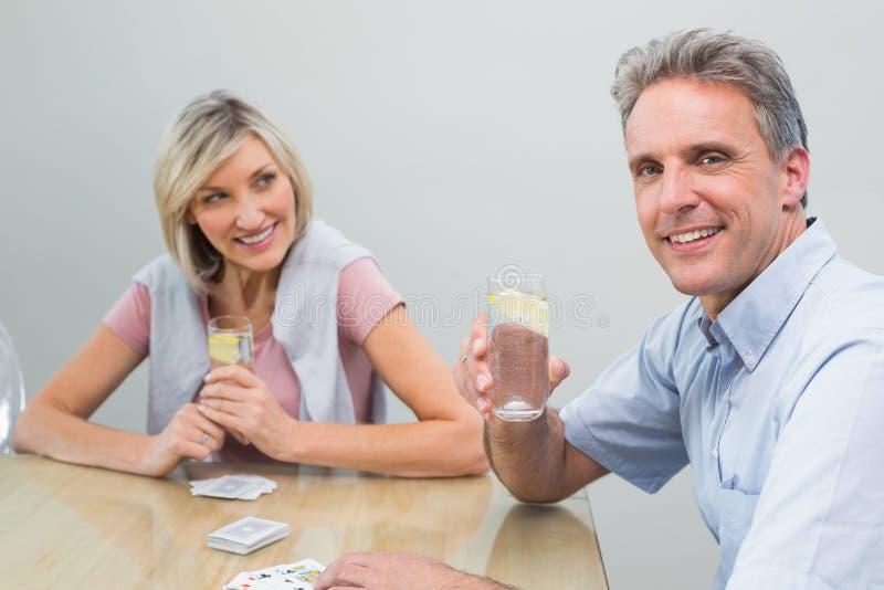 Ajouter aux jus de limette tout en jouant des cartes à la maison image stock