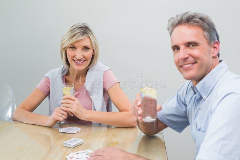 Ajouter aux jus de limette tout en jouant des cartes à la maison photo libre de droits