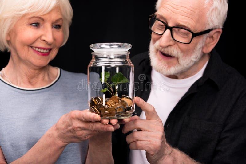 Ajouter aux pièces de monnaie et usine dans le pot images stock