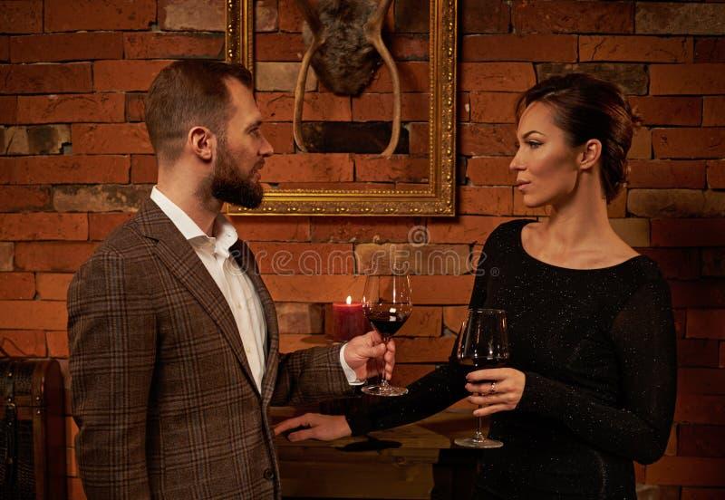 Ajouter bien habillés au verre de vin rouge dans l'intérieur à la maison confortable images libres de droits
