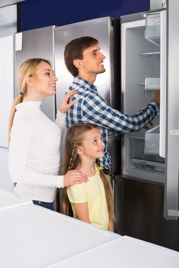 Download Ajouter De Sourire à La Fille Choisissant Le Réfrigérateur Photo stock - Image du consommationisme, home: 76083544