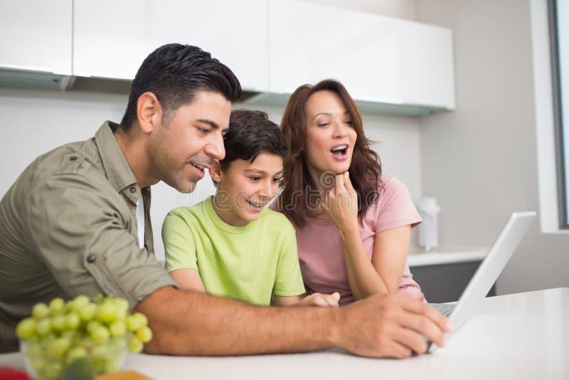 Ajouter de sourire au fils à l'aide de l'ordinateur portable image libre de droits