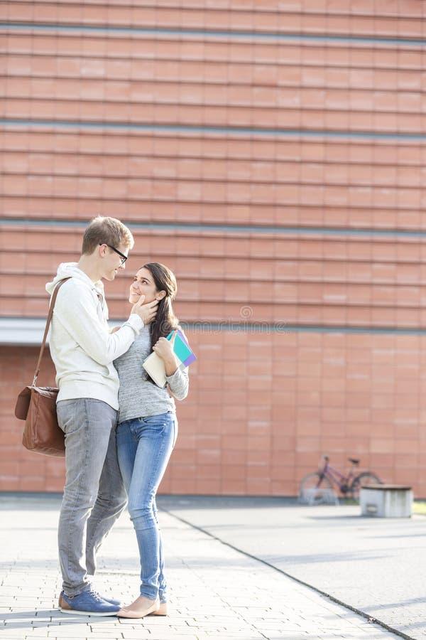 Ajouter de sourire aux livres se tenant au campus universitaire photos stock