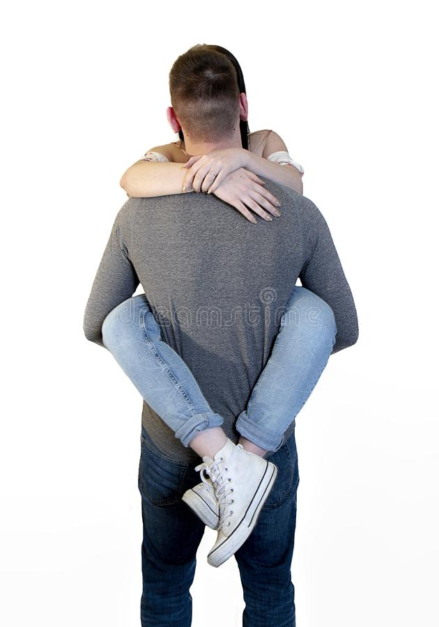 Ajouter espiègles à la jeune femme enroulée autour de la taille de l'ami d'isolement sur le blanc photographie stock