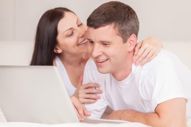Ajouter heureux à l'ordinateur portable dans le sourire de lit photographie stock libre de droits