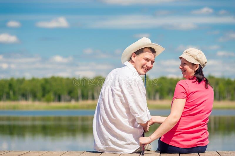 Ajouter heureux à une canne à pêche se reposant sur un pilier en bois image stock