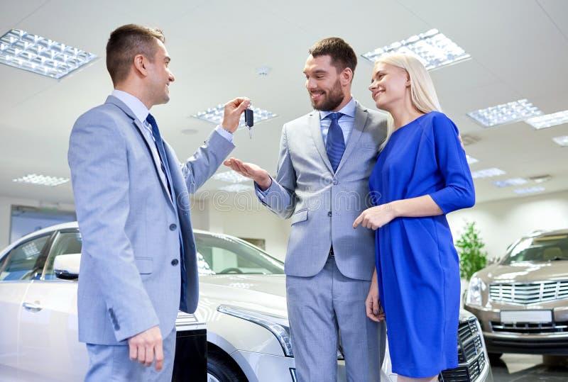 Ajouter heureux au concessionnaire automobile dans le salon de l'Auto ou le salon photos libres de droits