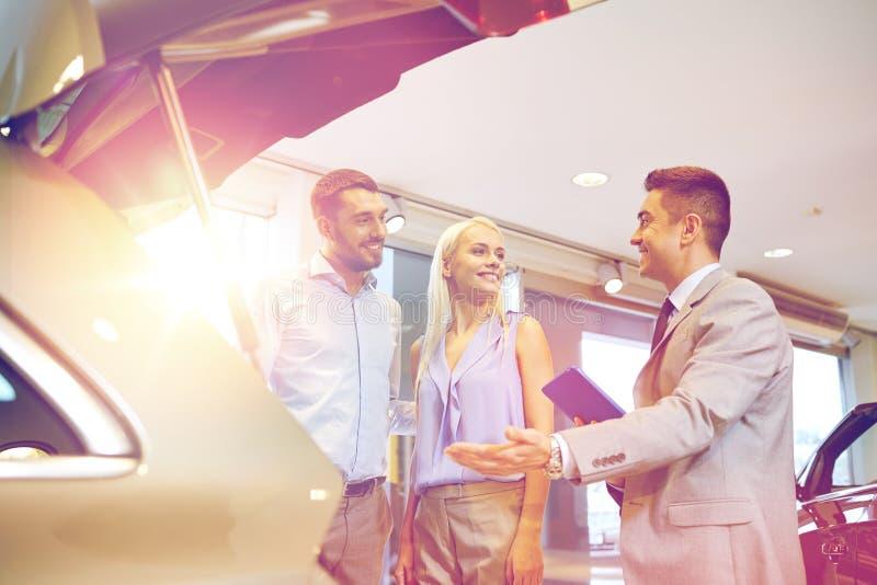 Ajouter heureux au concessionnaire automobile dans le salon de l'Auto ou le salon photographie stock