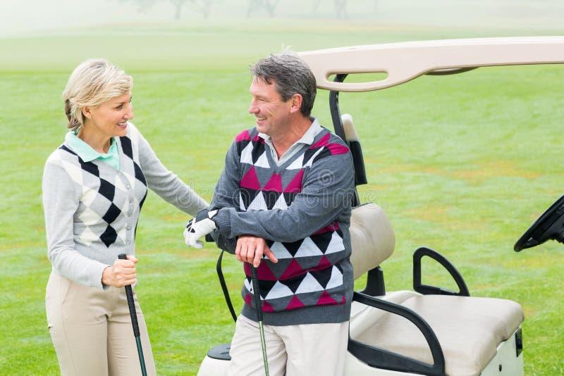 Ajouter jouants au golf heureux au boguet de golf derrière photographie stock libre de droits