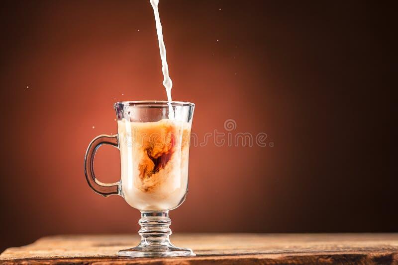 Ajouter le lait à une tasse de thé photographie stock libre de droits