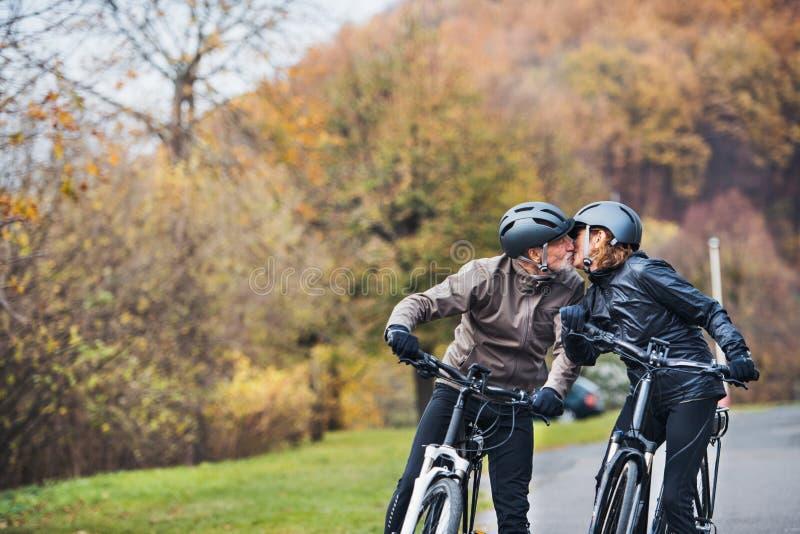 Ajouter supérieurs actifs aux electrobikes se tenant dehors sur une route en nature, embrassant images stock