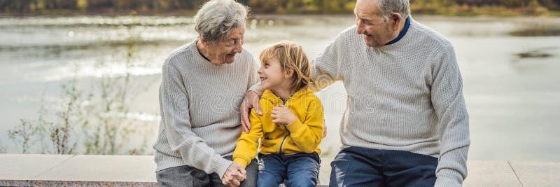 Ajouter supérieurs au petit-fils de bébé en parc d'automne BANNIÈRE d'arrière grand-mère, d'arrière-grand-père et d'arrière-petit photo stock