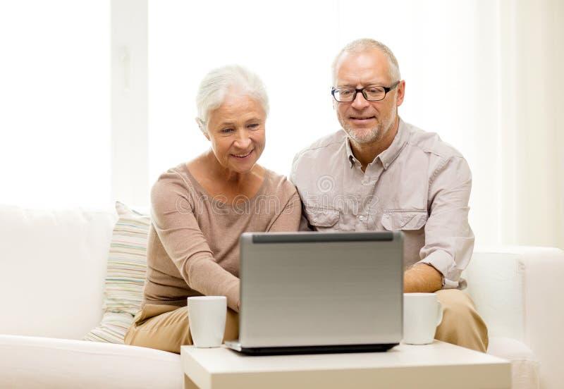Ajouter supérieurs heureux à l'ordinateur portable et aux tasses à la maison photo stock
