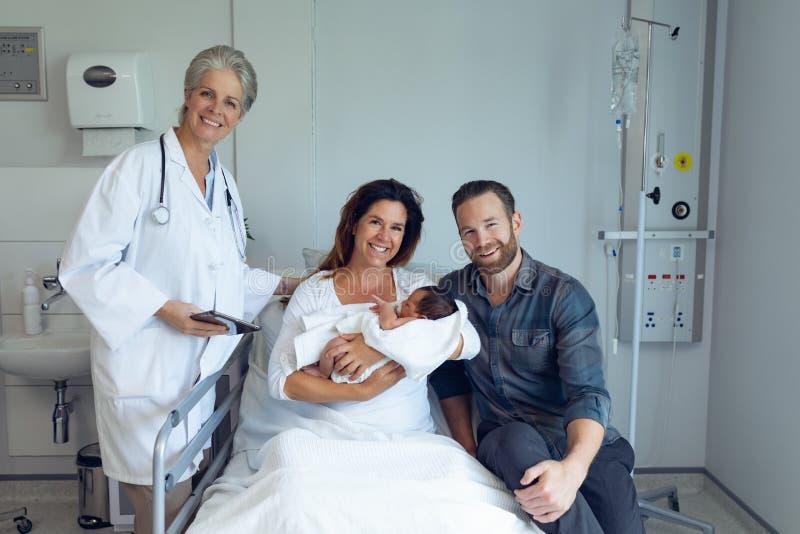 Ajoutez au docteur tenant leur bébé nouveau-né dans la salle photos libres de droits