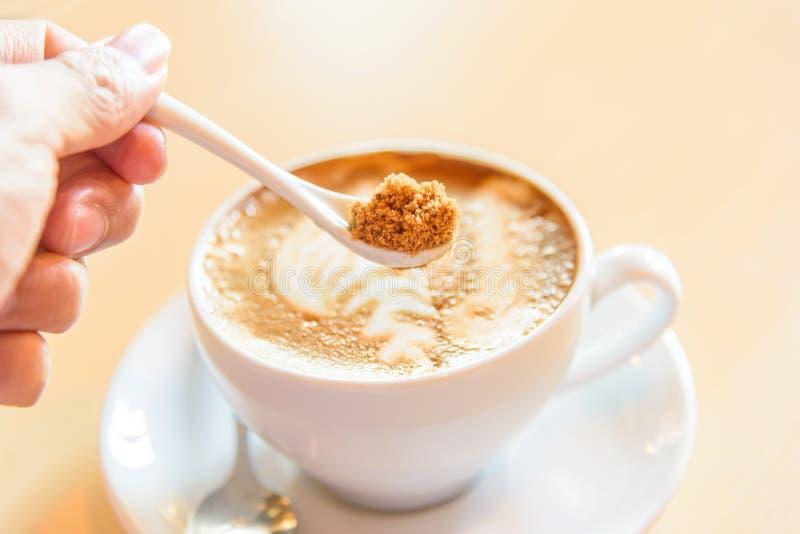 Ajoutez le sucre au café chaud images stock