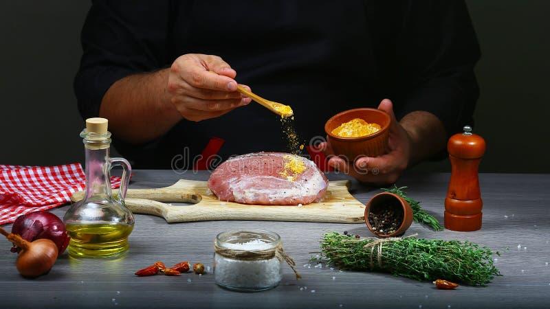 Ajoutez les épices au bifteck de boeuf avec le moulin dans des mains de chef, fond noir Photo de recette de nourriture, texte de  images stock