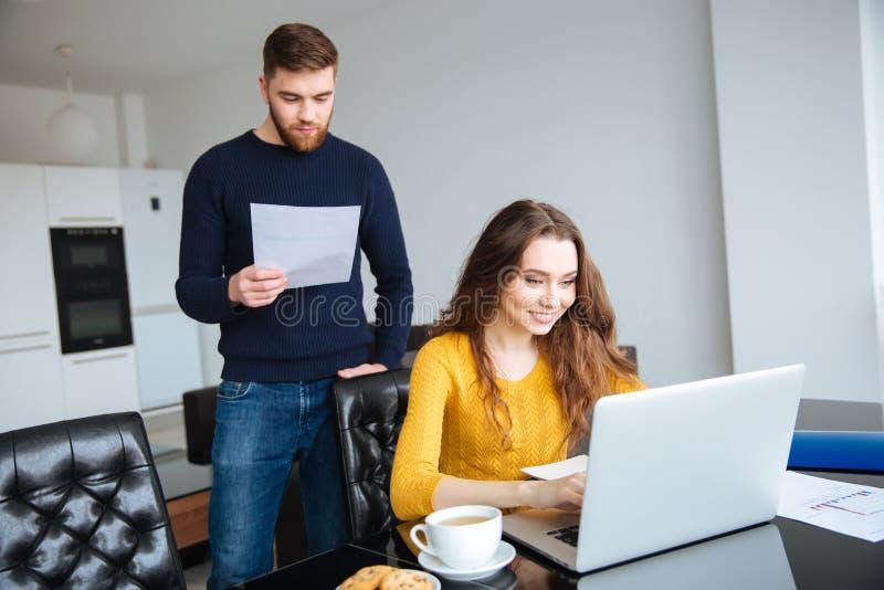 Ajoutez payer leurs factures en ligne à l'ordinateur portable à la maison photo libre de droits