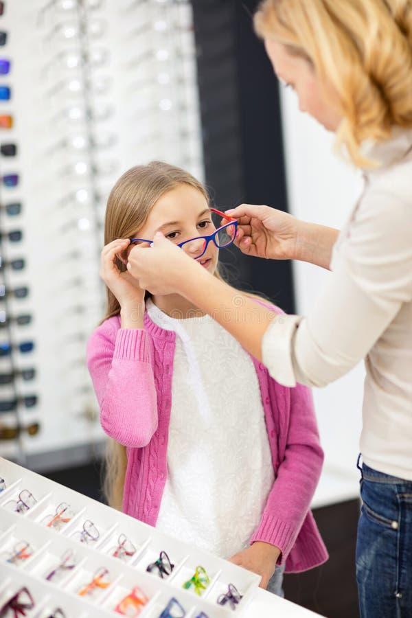 Ajuda da mãe sua filha para escolher vidros do quadro foto de stock royalty free